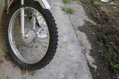Stäng sig upp det plana gummihjulet för hjulet av den sprucken motorcykeln som är gammal och Arkivbild