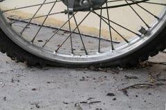 Stäng sig upp det plana gummihjulet för hjulet av den sprucken motorcykeln som är gammal och Royaltyfri Foto
