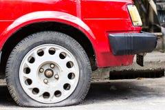 Stäng sig upp det plana gummihjulet på vänta för väg Arkivfoto