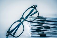 Stäng sig upp det svarta läs- glasögon på att stapla av kontorspape royaltyfria foton