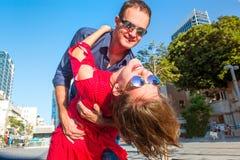 Stäng sig upp emotionella unga lyckliga par i ljus kläder och solglasögon som har roligt utomhus Le vänner som dansar i gatan fotografering för bildbyråer