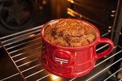 Stäng sig upp en stor frodig rödlätt mugcake i ett rött rånar lagat mat i ugnen Laga mat och muffinreceptrealism royaltyfria foton