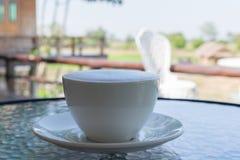 Stäng sig upp en vit kopp kaffe, latte med härligt mjölkar skum på den glass tabellen royaltyfri bild