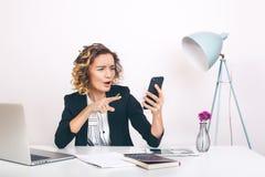 Stäng sig upp för affärskvinna för stående ungt lyckligt sammanträde på hennes skrivbord i ett kontor arbeta på en bärbar datorda Royaltyfria Bilder