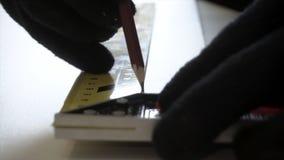 Stäng sig upp för ledar- händer för man i svarta handskar som markerar med en blyertspenna och en mäta linjal ett ställe för snit royaltyfri fotografi