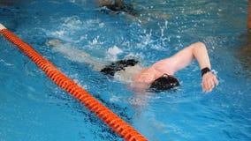 Stäng sig upp för yrkesmässig simmare i långsam mothion, medan simma loppet i inomhus pöl Idrottsman nenutbildning, simma royaltyfri foto