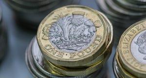 Stäng sig upp fokusfoto av det nya Förenade kungariket pundmyntet, bland andra brittiska mynt Royaltyfri Foto