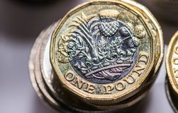 Stäng sig upp fokusfoto av det nya Förenade kungariket pundmyntet, bland andra brittiska mynt Arkivfoto