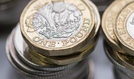 Stäng sig upp fokusfoto av det nya Förenade kungariket pundmyntet, bland andra brittiska mynt Arkivfoton