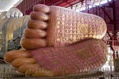 Stäng sig upp fot av att vila buddha på den Chauk-htat-gyi Buddha Templ royaltyfri bild
