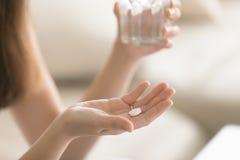 Stäng sig upp fotoet av den runda vita preventivpilleren i kvinnlig hand royaltyfri bild