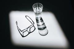 Stäng sig upp fotoet av exponeringsglas och exponeringsglas av vatten på kontorstabellen Exponeringsglas och exponeringsglas av k Fotografering för Bildbyråer