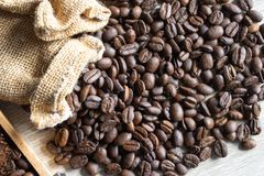 Stäng sig upp grillade kaffebönor i liten säck på trätabellen arkivbild