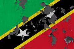 Stäng sig upp grungy, skadad och riden ut flagga för helgon Kitts och Nevis på väggen som skalar av målarfärg för att se inom ytt stock illustrationer