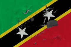 Stäng sig upp grungy, skadad och riden ut flagga för helgon Kitts och Nevis på väggen som skalar av målarfärg för att se inom ytt royaltyfri illustrationer