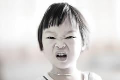 Stäng sig upp gullig asiatisk flicka med den ilskna framsidan Fotografering för Bildbyråer