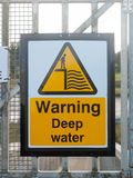Stäng sig upp gult tecken på skeppsdockan som varnar djupt vatten Royaltyfri Foto