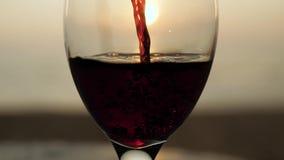 Stäng sig upp hällande rött vinexponeringsglas på solnedgången på landskap för sjösidasiktsdäck Havstranden vinkar makrocloseupen lager videofilmer