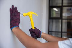 Stäng sig upp händer med handskar som att bulta spikar royaltyfria bilder