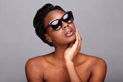 Stäng sig upp härlig svart kvinna med solglasögon och gör bar skuldror fotografering för bildbyråer