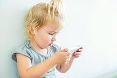 Stäng sig upp härligt litet behandla som ett barn flickainnehavet och att spela med den smarta telefonen på den vita väggbakgrund Royaltyfri Foto