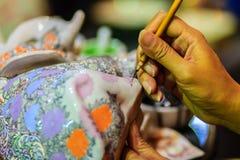 Stäng sig upp handen av den thailändska kvinnakonstnären under att måla masterpien Arkivbild