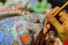 Stäng sig upp handen av den thailändska kvinnakonstnären under att måla masterpien Arkivfoton