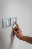 Stäng sig upp handen som vänder som är 'På/av' på gråa ljusa strömbrytare Arkivfoto