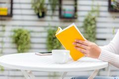 Stäng sig upp handkvinnor som bär tröjan, sammanträde och läsning en bok Royaltyfri Fotografi