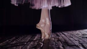 Stäng sig upp, i strålar av strålkastaren, på etapp av den gamla teaterkorridoren ballerina i den vita kjolen, lönelyfter på tår  lager videofilmer