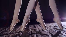 Stäng sig upp, i strålar av strålkastaren, på etappen av den gamla teaterkorridoren ballerina lyfter på tår i pointeskor, utför stock video