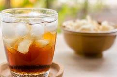 Stäng sig upp i torkad tioarmad bläckfisk och cola i exponeringsglas på träbakgrund Royaltyfria Bilder