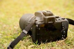 Stäng sig upp kameran DSLR på golv för grönt gräs Royaltyfri Fotografi