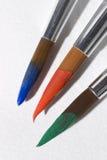 Stäng sig upp konstmålarfärgborstar som doppas med målarfärg Arkivbilder