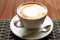 Stäng sig upp koppen av kaffe för hjärta för capuccinolattekonst på den wood backgrouen Fotografering för Bildbyråer