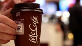Stäng sig upp kvinnan som tar den Mccafe kaffeklistermärken och förlägger på kortet för att samla fritt kaffe arkivfilmer