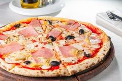 Stäng sig upp läcker köttpizza med bacon, hönafilén, skivade champinjoner och oliv på träbrädet på set Royaltyfri Bild