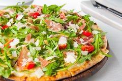 Stäng sig upp läcker pizza med skivor för hamon och för den körsbärsröda tomaten, parmezan ost och arugula på träbrädet på t Royaltyfri Bild