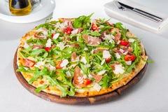Stäng sig upp läcker pizza med skivor för hamon och för den körsbärsröda tomaten, parmezan ost och arugula på träbrädet på t Royaltyfri Foto