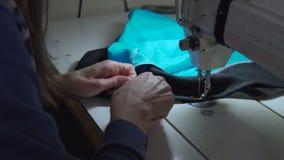 Stäng sig upp längd i fot räknat av en kvinna som syr en bomull med en symaskin lager videofilmer