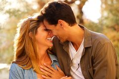 Stäng sig upp lyckliga par som står skratta tillsammans i nära omfamning royaltyfri fotografi