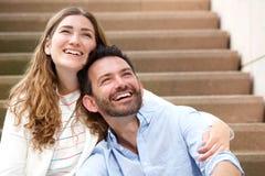 Stäng sig upp lyckliga par som tillsammans sitter på trappuppgång i omfamning Fotografering för Bildbyråer