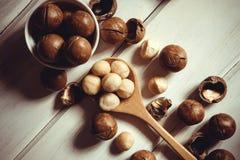 Stäng sig upp Macadamiamuttrarna på vit träbakgrund, superf arkivfoton
