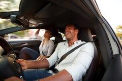 Stäng sig upp mannen och kvinnan som tillsammans ler och sitter i bil arkivfoton