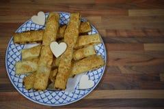 Stäng sig upp matfotografi av traditionella engelska hemlagade ostsugrör på en platta med förälskelsehjärtagarneringar arkivfoto