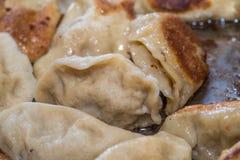 Stäng sig upp matlagning stekte klimpar i en stekpanna Kinesisk mat med varmt ångar Royaltyfri Foto
