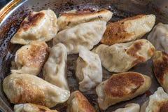 Stäng sig upp matlagning stekte klimpar i en stekpanna Kinesisk mat med varmt ångar Arkivfoton