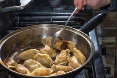 Stäng sig upp matlagning stekte klimpar i en stekpanna Kinesisk mat med varmt ångar Arkivbild
