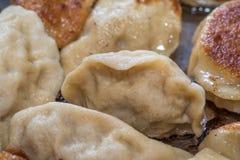 Stäng sig upp matlagning stekte klimpar i en stekpanna Kinesisk mat med varmt ångar Fotografering för Bildbyråer
