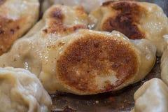 Stäng sig upp matlagning stekte klimpar i en stekpanna Kinesisk mat med varmt ångar Royaltyfri Fotografi